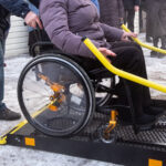 Winter. A woman in a wheelchair on a lift of a specialized vehicle for people with disabilities. Taxi for the disabled. Yellow bar and handrail.